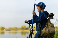 A fisherman boy on the river bank with a fishing rod in his hand. A child on a bicycle with a backpack on the shore of the river with fishing accessories.It Stock Photos