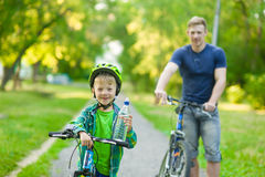 Child on a bicycle with father in the park Stock Photos