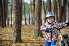 Child on a bicycle in the forest in early morning. Boy cycling o Stock Image