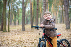 Child on a bicycle in the forest in early morning. Boy cycling o Royalty Free Stock Photography