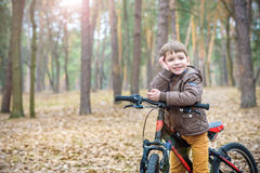 Child on a bicycle in the forest in early morning. Boy cycling o Stock Photography