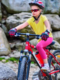 Child on bicycle ride mountain. Girl traveling in summer park. Cycling person wearing helmet . Sport trip is good for children health Royalty Free Stock Images
