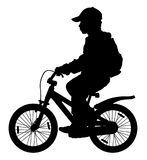 Child on a bicycle silhouette. Royalty Free Stock Images