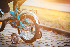 Child on a bicycle  in sunny day. Back view. Stock Photo