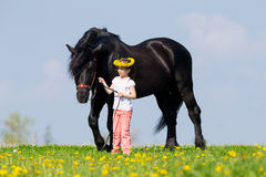 Child and big black horse in field Royalty Free Stock Photos