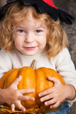 Child with big pumpkin. Happy smiling child in hat of witch holding a big orange pumpkin. Halloween concept Stock Images