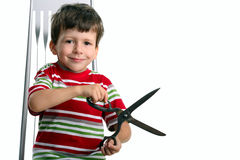 Child with big scissors sit on chair Stock Image
