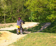 Girl on bike in park. Young girl riding bike on dirt path in park on sunny day stock images