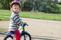 Child with bike. Child girl with the safety helmet on the bike in the autumn park royalty free stock photography