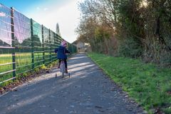 Child on the bike looking back and smiling on the path by the fence royalty free stock image