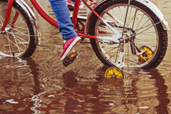 Child on bike rides through a puddle in autumn day. Child on a bicycle at asphalt road in summer. Bike in the park moving through puddle on rainy day Stock Image