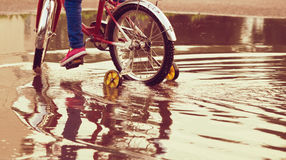 Child on bike rides through a puddle in autumn day. Child on a bicycle at asphalt road in summer. Bike in the park moving through puddle on rainy day Royalty Free Stock Images