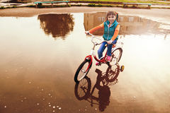 Child on bike rides through a puddle in autumn day. Royalty Free Stock Photo