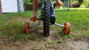 Child on bike with training wheels in dirt Royalty Free Stock Photo