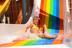 Child in bikini sliding water park. Girl in yellow bikini sliding water park Stock Photo