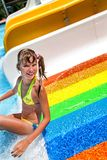 Child in bikini sliding water park. Girl in yellow bikini sliding water park Stock Images