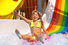Child in bikini sliding water park. Happy child girl in bikini sliding water park Stock Photos