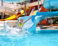 Child in bikini sliding water park. Happy child girl in bikini sliding water park Royalty Free Stock Photos