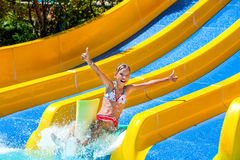Child in bikini sliding water park. Happy child girl in bikini sliding water park and shoe thumb up Stock Photos