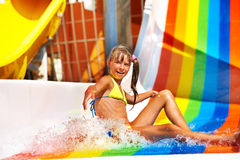 Child in bikini sliding water park. Happy child girl in yellow bikini sliding water park Royalty Free Stock Images