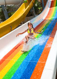 Child in bikini sliding water park. Happy child girl in yellow bikini sliding water park Royalty Free Stock Photography
