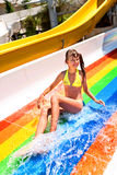 Child in bikini sliding water park. Happy child girl in yellow bikini sliding water park Royalty Free Stock Photos