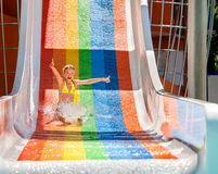Child in bikini sliding water park. Happy child girl in yellow bikini sliding water park Royalty Free Stock Image