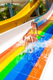 Child in bikini sliding water park. Happy child girl in yellow bikini sliding water park. Hot weather Stock Images