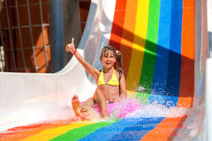 Child in bikini sliding water park. Happy child girl in yellow bikini sliding water park and show thumb up Royalty Free Stock Photos