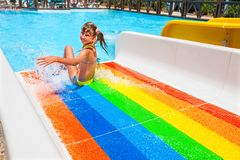 Child in bikini sliding water park. Happy child girl in yellow bikini sliding striped water park Stock Photography