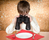 Child with binoculars. Child looks at a plate throught a binoculars Stock Photography