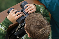 Child and binoculars. A child researches world with  binocular on  look-tower Royalty Free Stock Image