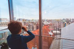 Child looking at roofs of Amsterdam. Child with binoculars looking at colorful roofs and buildings of Amsterdam from above, travel destination concept with copy royalty free stock photo