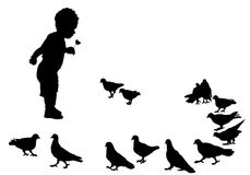 Child and birds. Child feeding pigeons on a walk in the city park Royalty Free Stock Image