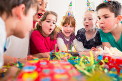 Child on birthday party blowing candles on cake Royalty Free Stock Images