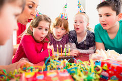 Child on birthday party blowing candles on cake Royalty Free Stock Photos