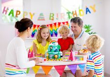Child birthday party cake. Family with kids. Kids birthday party. Child blowing candles on cake and opening presents on jungle theme celebration. Family royalty free stock image