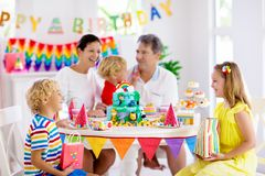 Child birthday party cake. Family with kids. Kids birthday party. Child blowing candles on cake and opening presents on jungle theme celebration. Family stock images