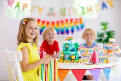 Child birthday party. Kids blow candle on cake. Kids birthday party. Child blowing candles on cake and opening presents on jungle theme celebration. Cakes royalty free stock photos