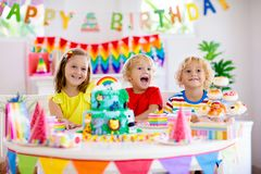 Child birthday party. Kids blow candle on cake. Kids birthday party. Child blowing candles on cake and opening presents on jungle theme celebration. Cakes stock photo