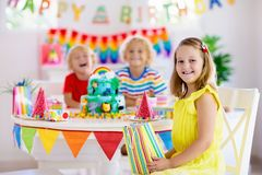 Child birthday party. Kids blow candle on cake. Kids birthday party. Child blowing candles on cake and opening presents on jungle theme celebration. Cakes royalty free stock photography