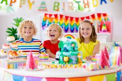 Child birthday party. Kids blow candle on cake. Kids birthday party. Child blowing candles on cake and opening presents on jungle theme celebration. Cakes royalty free stock image