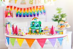 Child birthday party. Kids blow candle on cake. Kids birthday party. Child blowing candles on cake and opening presents on jungle theme celebration. Cakes royalty free stock images