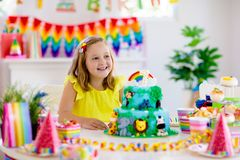 Child birthday party. Kids blow candle on cake. Kids birthday party. Child blowing candles on cake and opening presents on jungle theme celebration. Sweets and stock photos