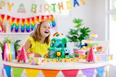 Child birthday party. Kids blow candle on cake stock images