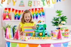Child birthday party. Kids blow candle on cake. Kids birthday party. Child blowing candles on cake and opening presents on jungle theme celebration. Sweets and stock images