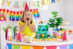 Child birthday party. Kids blow candle on cake. Kids birthday party. Child blowing candles on cake and opening presents on jungle theme celebration. Sweets and royalty free stock images