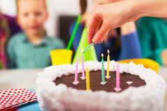 Child on birthday party prepared blowing candles on cake, selective focus royalty free stock photos