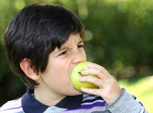Child bite on a apple in the middle of the lawn Stock Image