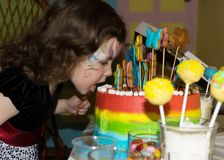 Child bite a rainbow cake.  royalty free stock images